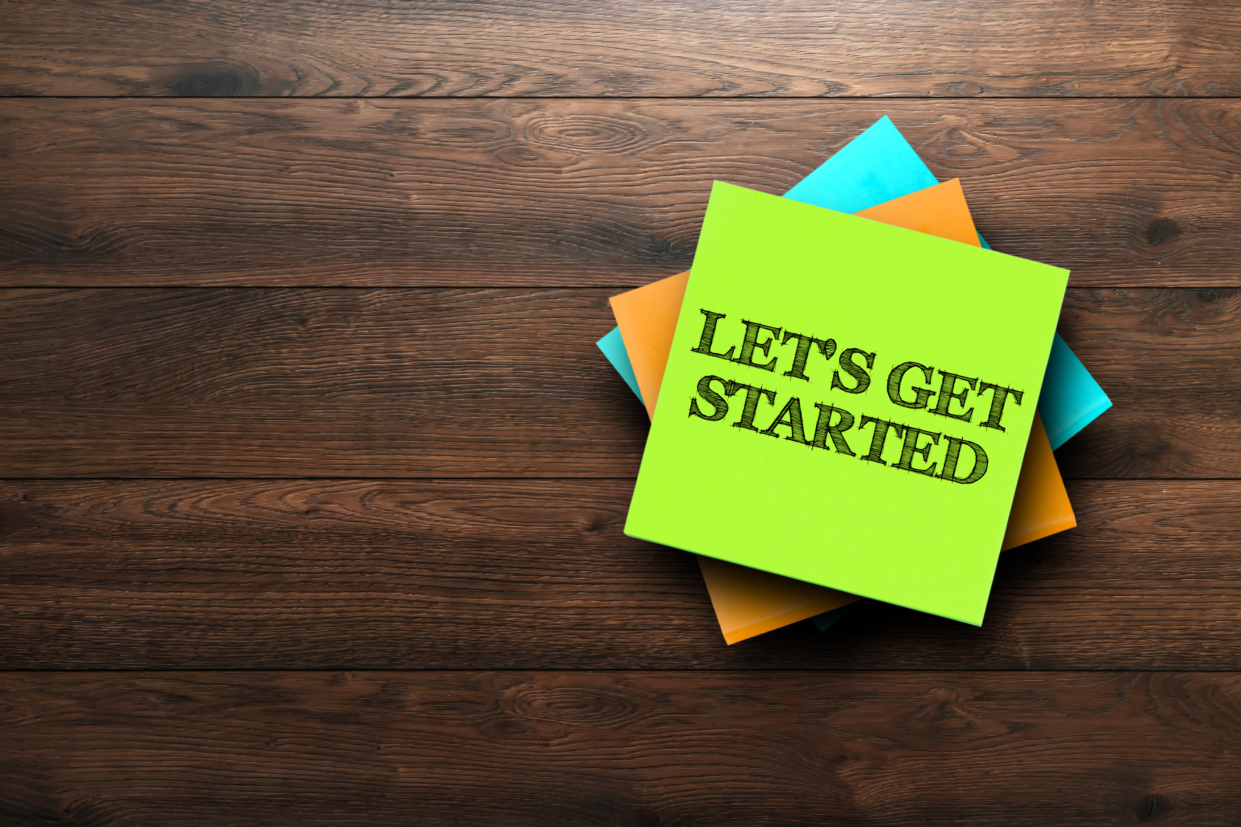 Let's-Get-Started,-the-phrase-is-written-on-multi-colored-stickers,-on-a-brown-wooden-background.-Business-concept,-strategy,-plan,-planning.-956959350_4000x2667