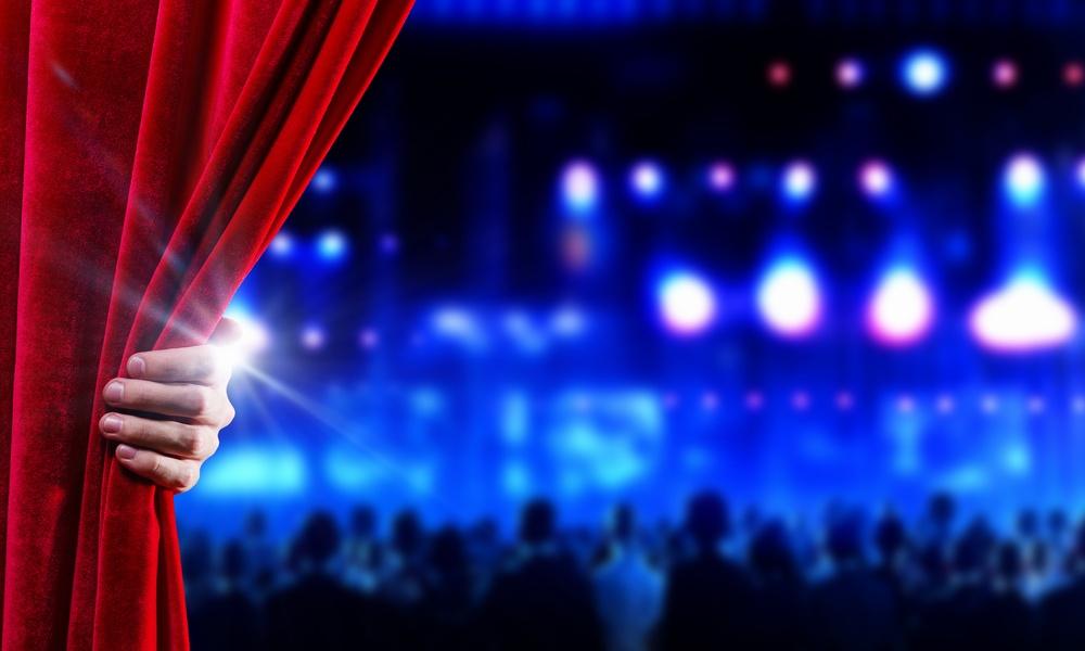 Hand of businessman opening red velvet curtain.jpeg